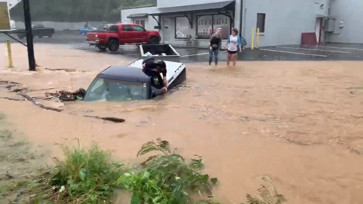 A group of bystanders pulled together, literally, to save a stranger after his truck was submerged in floodwater in Winston-Salem Thursday.