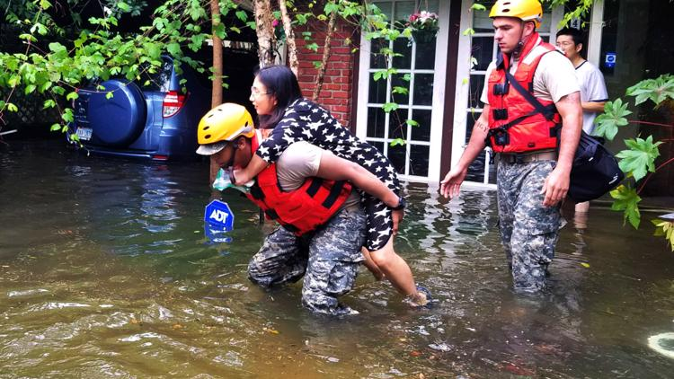 In this handout provided by the Army National Guard, A Texas National Guardsman carries a resident from her flooded home following Hurricane Harvey August 27, 2017 in Houston, Texas.