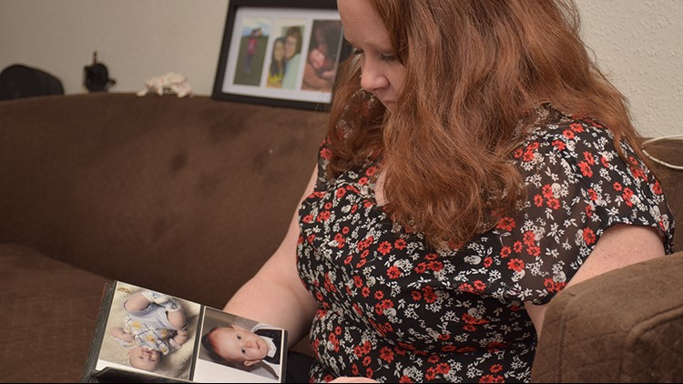 Dee Dee Estis looks through an album filled with photos of her 3-year-old son.