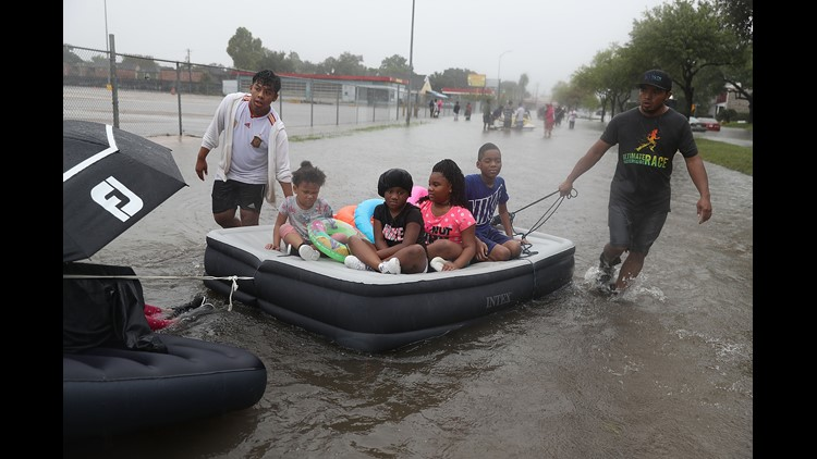 People use an air matress to float down a flooded street as they evacuate their homes after the area was inundated with flooding from Hurricane Harvey on August 27, 2017 in Houston, Texas.