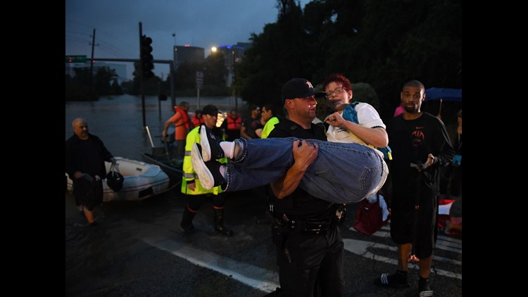A woman is carried after being rescued from a hotel by boat due to heavy flooding by Hurricane Harvey in Houston, Texas on August 27, 2017.